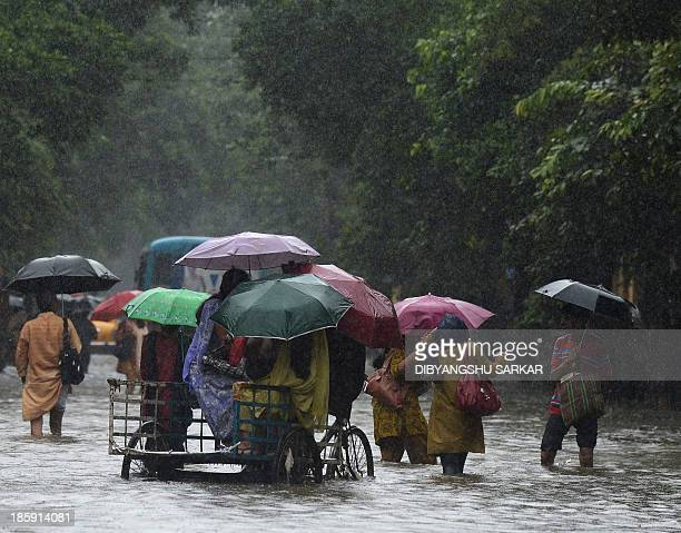 An Indian rickshaw puller carries students through waterlogged streets in Kolkata on October 26 2013 Persistent rain for the last 24 hours has thrown...