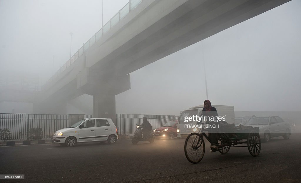 An Indian rickshaw puller passes under a bridge early in New Delhi on January 31, 2013. Air Quality Index (AQI) pollution markers were at hazardous levels around the city. AFP PHOTO/ Prakash SINGH