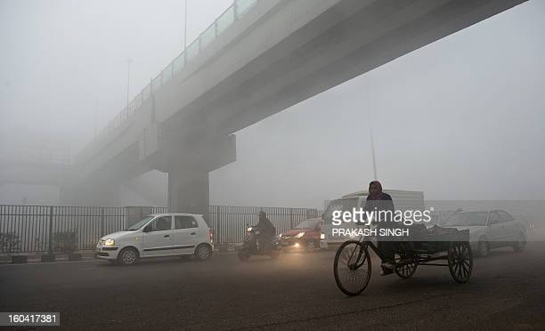 An Indian rickshaw puller passes under a bridge early in New Delhi on January 31 2013 Air Quality Index pollution markers were at hazardous levels...
