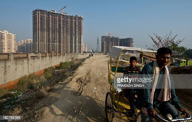 An Indian rickshaw puller rides past a highrise residential complex undergoing construction in Ghaziabad on the outskirts of New Delhi on February 27...
