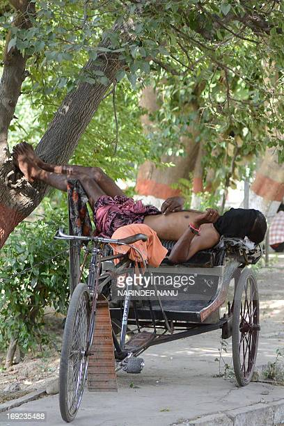 An Indian rickshaw puller sleeps in the shade on his rickshaw in Amritsar on May 22 2013 The entire north of the country and various other parts are...