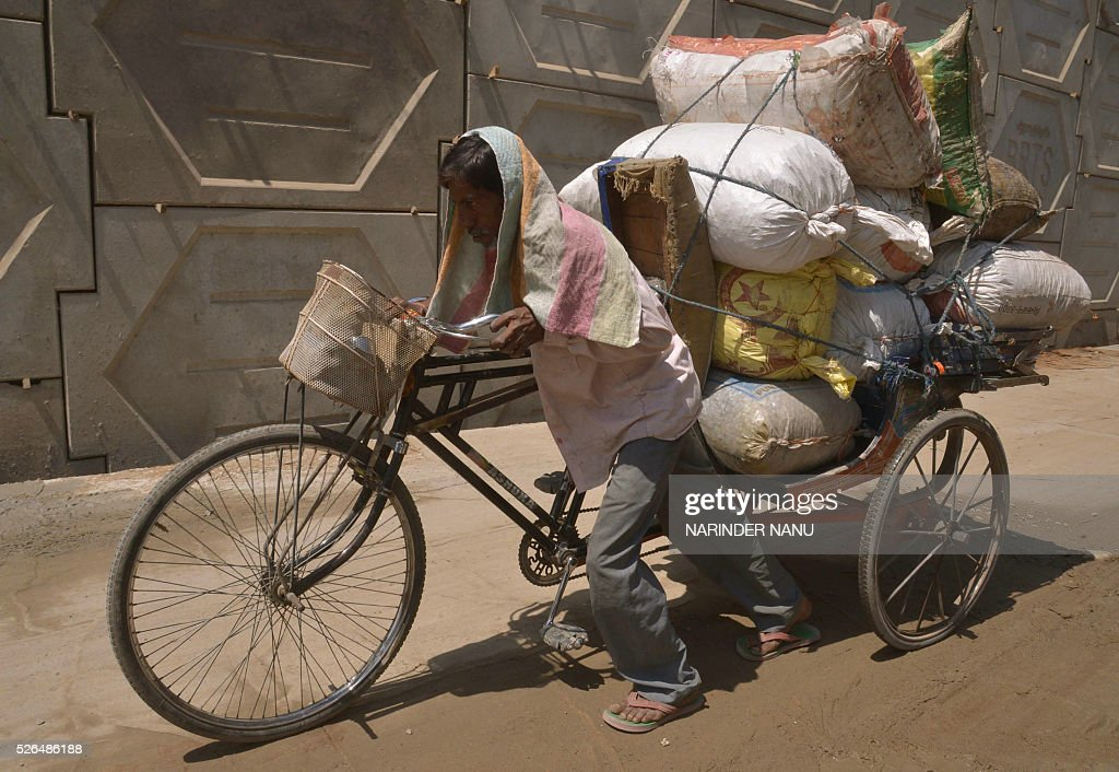 An Indian rickshaw puller transports empty glass medicine bottles during a hot afternoon in Amritsar on April 30, 2016. Hundreds of mainly poor people die at the height of summer annually in India, but temperatures have risen earlier than normal, increasing concerns about this year's overall toll. / AFP / NARINDER
