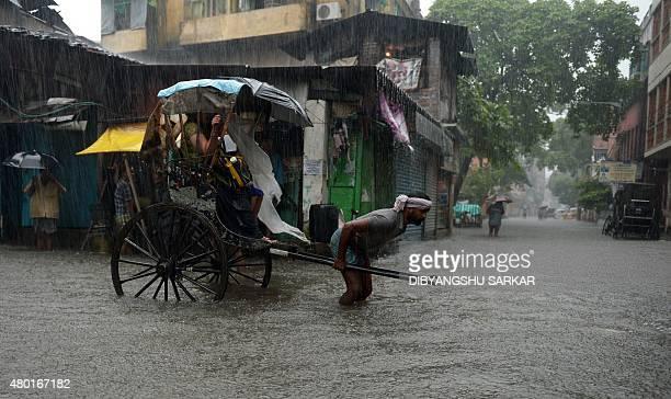 An Indian rickshaw puller transports passengers along a waterlogged street during heavy rain in Kolkata on July 10 2015 AFP PHOTO/ Dibyangshu Sarkar