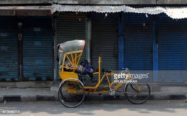 TOPSHOT An Indian rickshaw rider takes a nap next to shuttered stores during a statewide strike in support of farmers in Chennai on April 25 2017...