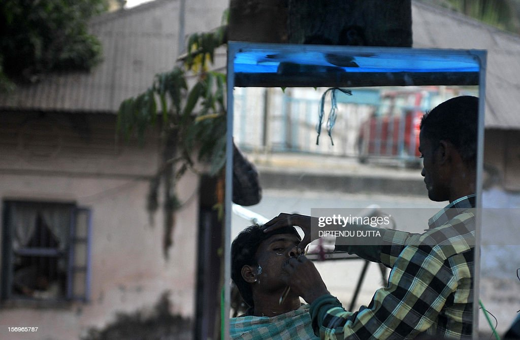 An Indian roadside barber attends to a customer in Siliguri on November 26, 2012. India's economy logged around 5.5 percent growth in the last financial quarter, the finance minister estimated on November 24, 2012 - a rate that could boost calls for lower interest rates to spur activity. AFP PHOTO/Diptendu DUTTA