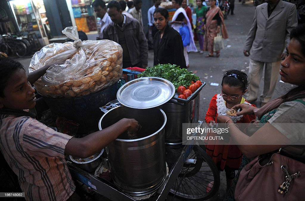 An Indian roadside food vendor serves golgappa, known locally as fuchka, at a market in Siliguri on November 20, 2012. the snack, popular in South Asia, consists of a round hollow fired crisp and filled with a mixture of water containing potato, onion, chili, chickpeas, tamarind and chaat masala. AFP PHOTO/Diptendu DUTTA
