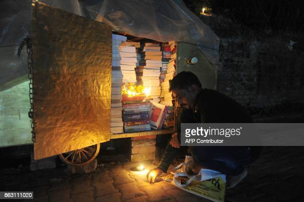 An Indian roadside shopkeeper lights candles on his cart after performing a puja to celebrate Diwali the Festival of Lights in Allahabad on October...