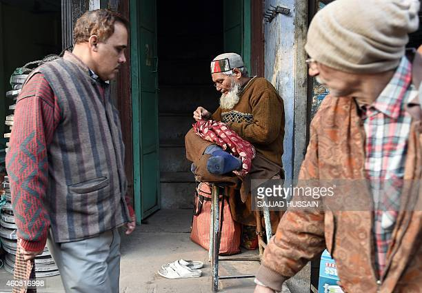 An Indian roadside tailor repairs a piece of cloth by interweaving yarn with a needle in the old quarters of New Delhi on December 24 2014 India has...