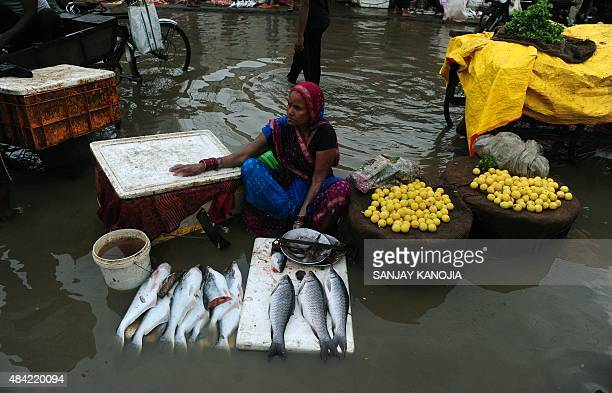An Indian roadside vendor selling fish waits for customers at her partially submerged roadside pitch in Allahabad on August 16 after heavy monsoon...