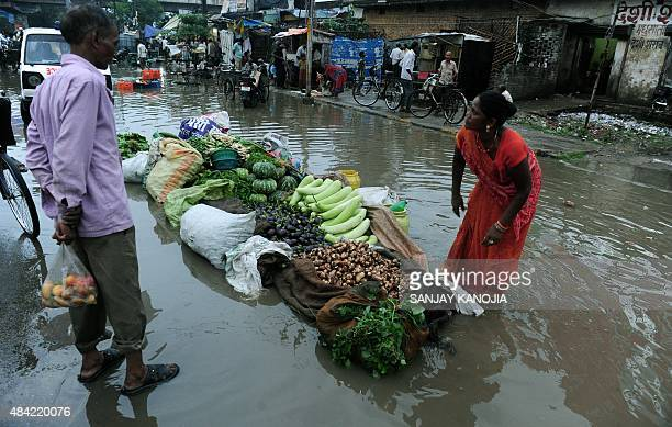 An Indian roadside vendor selling vegetables speaks with a customer at her partially submerged roadside pitch in Allahabad on August 16 after heavy...