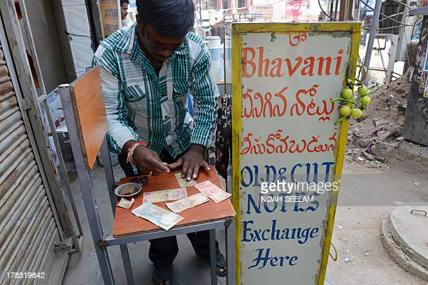 An Indian rupee note exchanger who trades new notes for his customers' damaged and worn bills while taking a two rupee commission for every ten...