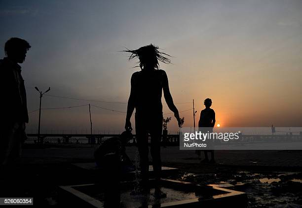 An Indian sadhu dries up his hairs after taking bathin Allahabad on June 112015