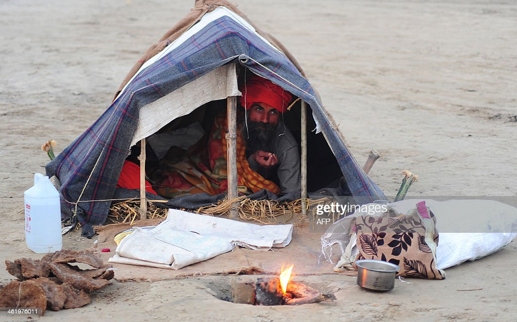 An Indian sadhu holy man lies in his tent on a cold winter day at Sangam in Allahabad on January 12 2014 AFP PHOTO/SANJAY KANOJIA