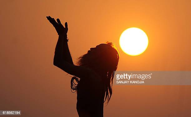 TOPSHOT An Indian sadhu holy man performs yoga at sunrise at the Dashashwamedh Ghat in Varanasi on October 27 2016 / AFP / SANJAY KANOJIA