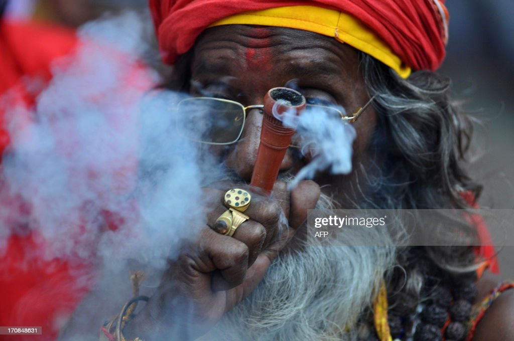 An Indian sadhu - holy man - puffs cannabis at the Kamakhya temple in Guwahati on June 19, 2013. Thousands of devotees from all over India gather on occasion of Ambubachi Mela, which is celebrated to mark the menstruation period of the goddess and during which occasion the sanctorum of the shrine remains closed to worshippers. The Ambubachi Mela runs from June 22-23. AFP PHOTO/Biju Boro