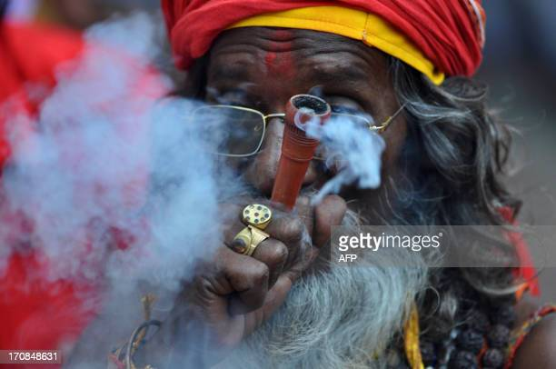 An Indian sadhu holy man puffs cannabis at the Kamakhya temple in Guwahati on June 19 2013 Thousands of devotees from all over India gather on...