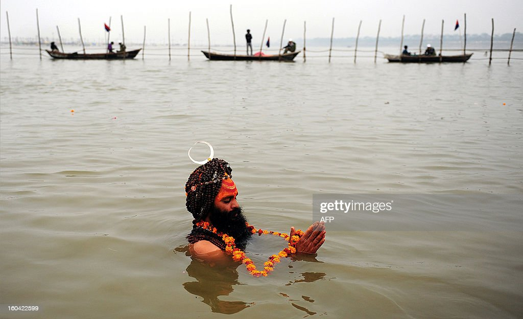 An Indian sadhu - holy man - takes a 'holy dip' at the 'Sangam', the confluence of the rivers Ganges, Yamuna and mythical Saraswati during the Maha Kumbh festival in Allahabad on January 31, 2013. The Kumbh Mela in the town of Allahabad will see up to 100 million worshippers gather over 55 days to take a ritual bath in the holy waters, believed to cleanse sins and bestow blessings. AFP PHOTO/Sanjay KANOJIA