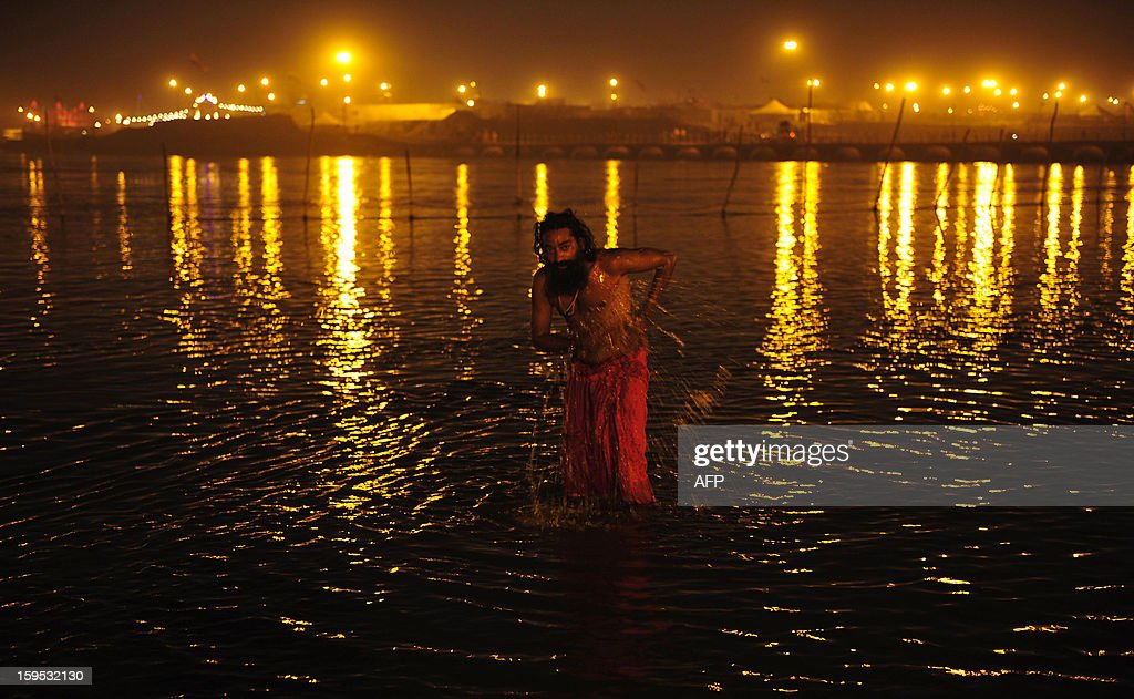 An Indian Sadhu - holy man - takes a 'holy dip' on the bank of the Ganga River as the lights of the 'tent city' twinkle during the Maha Kumbh Mela in Allahabad on January 15, 2013. The Kumbh Mela in the Indian town of Allahabad will see up to 100 million worshippers gather over the next 55 days to take a ritual bath in the holy waters, believed to cleanse sins and bestow blessings. AFP PHOTO/ Sanjay KANOJIA