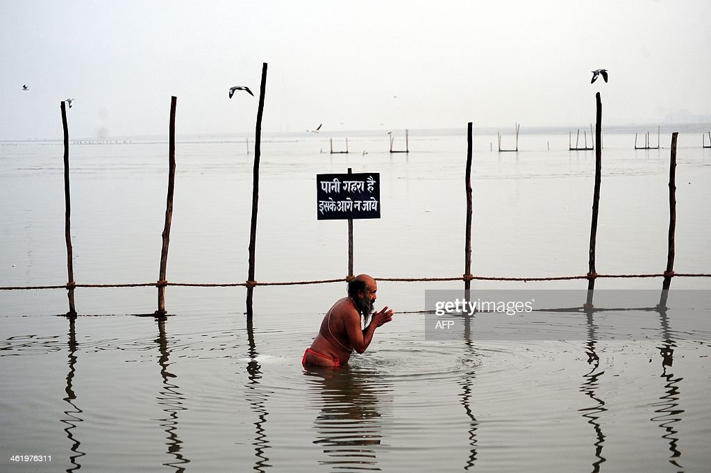 An Indian 'sadhu' holy man takes a 'holy dip' prior to the upcoming monthlong Hindu 'Magh Mela' festival at Sangam in Allahabad on January 12 2014...