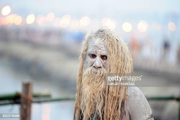 TOPSHOT An Indian Sadhu looks on after bathing in the River Ganges and smearing his body with ash during the Magh Mela festival in Allahabad on...