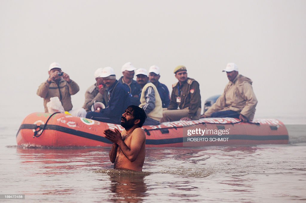 An Indian Sadhu or holy man prays in the waters of the Sangham or the confluence of the the Yamuna and Ganges rivers as authorities ride an inflatable boat past him during the Kumbh Mela in Allahabad on January 14, 2013. Hundreds of thousands of Hindu pilgrims led by naked, ash-covered holy men streamed into the sacred river Ganges at the start of the world's biggest religious festival. The Kumbh Mela in the Indian town of Allahabad will see up to 100 million worshippers gather over the next 55 days to take a ritual bath in the holy waters, believed to cleanse sins and bestow blessings.
