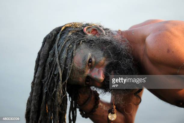 An Indian sadhu or holy man washes his hair with mud at Sangam the confluence of the rivers Ganges Yamuna and the mythical Saraswati in Allahabad on...