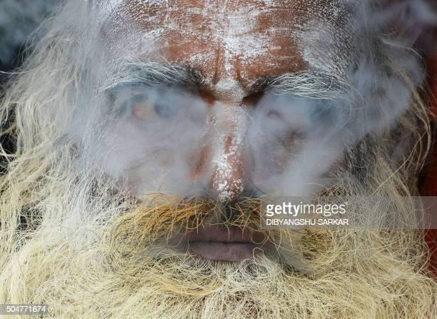 TOPSHOT An Indian sadhu smokes cannabis at his temporary camp on Gangasagar Island around 150 km south of Kolkata on January 13 2016 More than 500000...