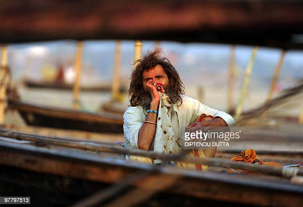 An Indian sadhu smokes on a boat on the river Ganges at Sangam the confluence of the Ganges Yamuna and Saraswati rivers in Allahabad on March 17 2010...