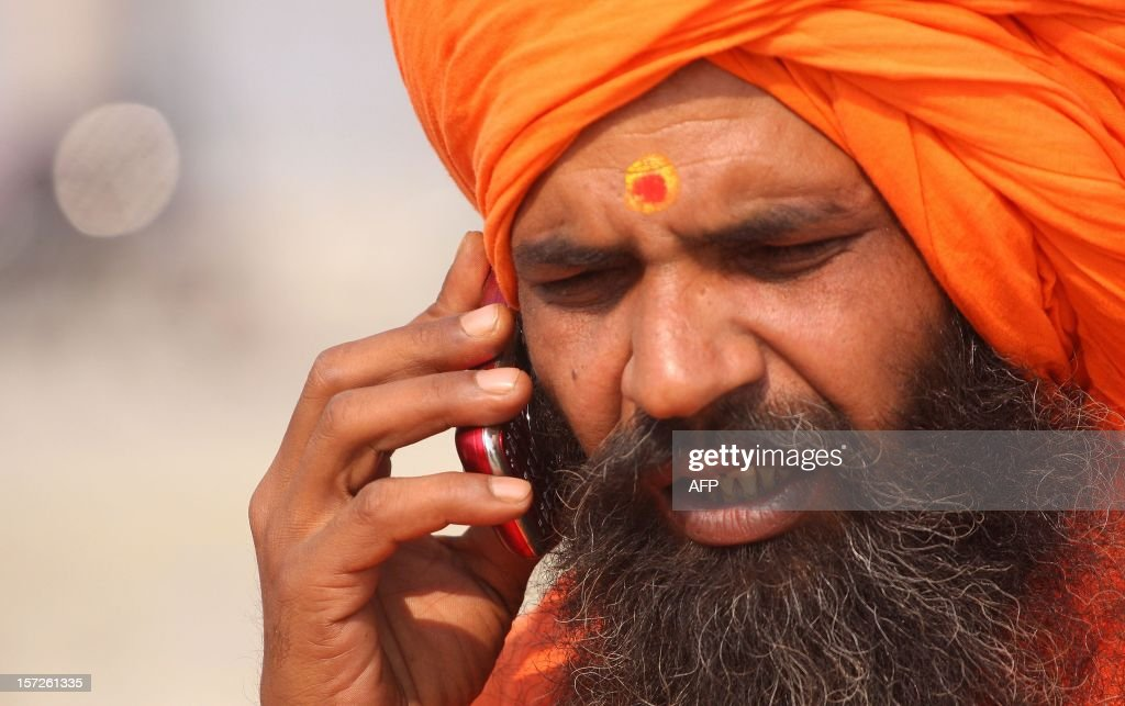 An Indian Sadhu speaks on a mobile phone after being allocated land for the 'Maha Kumbh Mela' in Allahabad on December 1, 2012. Allahabad, located in the north Indian state of Uttar Pradesh and where the Ganges, Yamuna and Saraswati rivers meet, is a focal point for Hindu pilgrims during The Maha Kumbh Mela, where millions of devotees gather to bathe every twelve years in the holy waters of the three rivers. AFP PHOTO/ Sanjay KANOJIA