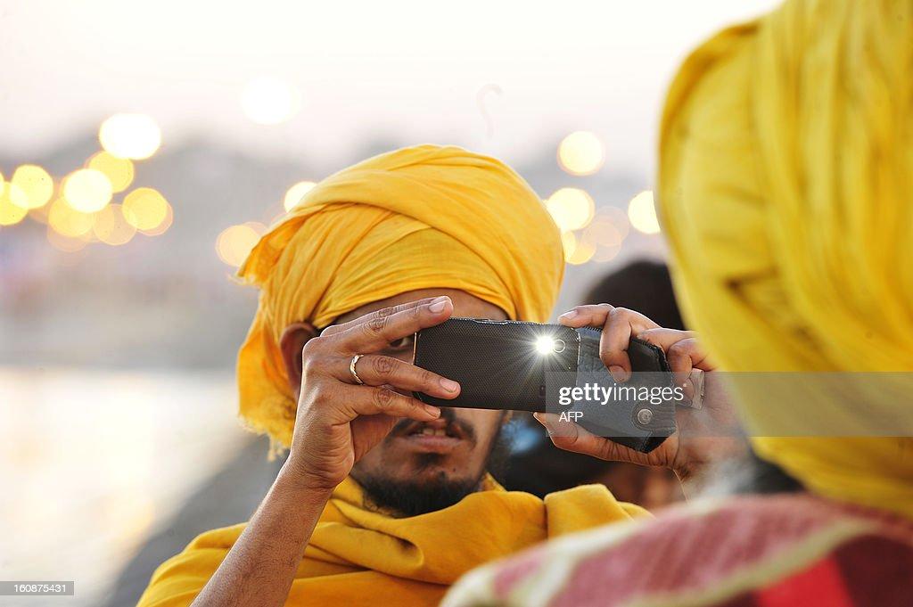 An Indian Sadhu take photograph from his mobile phone at the Sangam during the Maha Kumbh festival in Allahabad on February 7, 2013. The Kumbh Mela in the town of Allahabad will see up to 100 million worshippers gather over 55 days to take a ritual bath in the holy waters, believed to cleanse sins and bestow blessings. AFP PHOTO/Sanjay KANOJIA