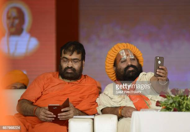 An Indian Sadhu takes a 'selfie' with a cellular telephone as he attends a gathering of The Vishva Hindu Parishad at The GMDC grounds in Ahmedabad on...