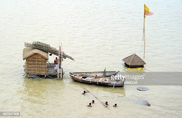 An Indian Sadhu watches as others help to move his belongings to drier ground after his hut was surrounded by floodwaters as the water level of the...