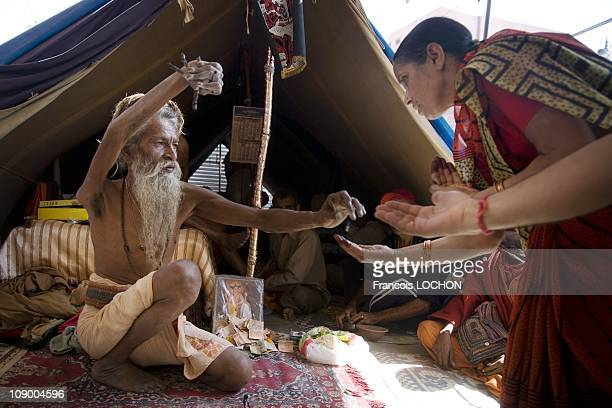 An Indian Sadhu who has kept his hand raised for more than 20 years gives blessings to Hindu devotees in a Sadhu camp during the Kumbh Mela Festival...