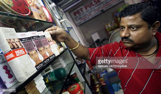 WITH 'INDIALIFESTYLECONSUMERRETAIL' An Indian salesman arranges men fairness products at a shop in New Delhi 04 September 2007 In a new commercial on...