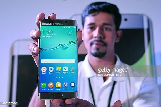 An Indian salesman poses for a photograph during the launch of the of Galaxy S6 Edge smartphone range in Bangalore on August 26 2015 AFP PHOTO /...