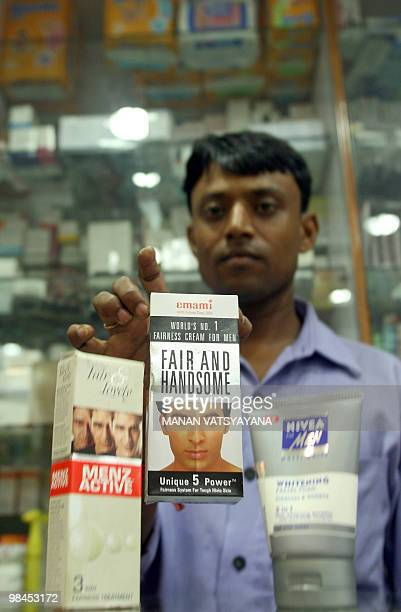 WITH 'INDIALIFESTYLECONSUMERRETAIL' An Indian salesman poses with men fairness products at a shop in New Delhi 04 September 2007 In a new commercial...