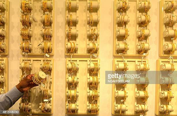 An Indian salesperson shows gold bracelets to a customer at a jewellers in Hyderabad on July 22 2015 Gold fell by INR 108 to trade at INR 24689 per...
