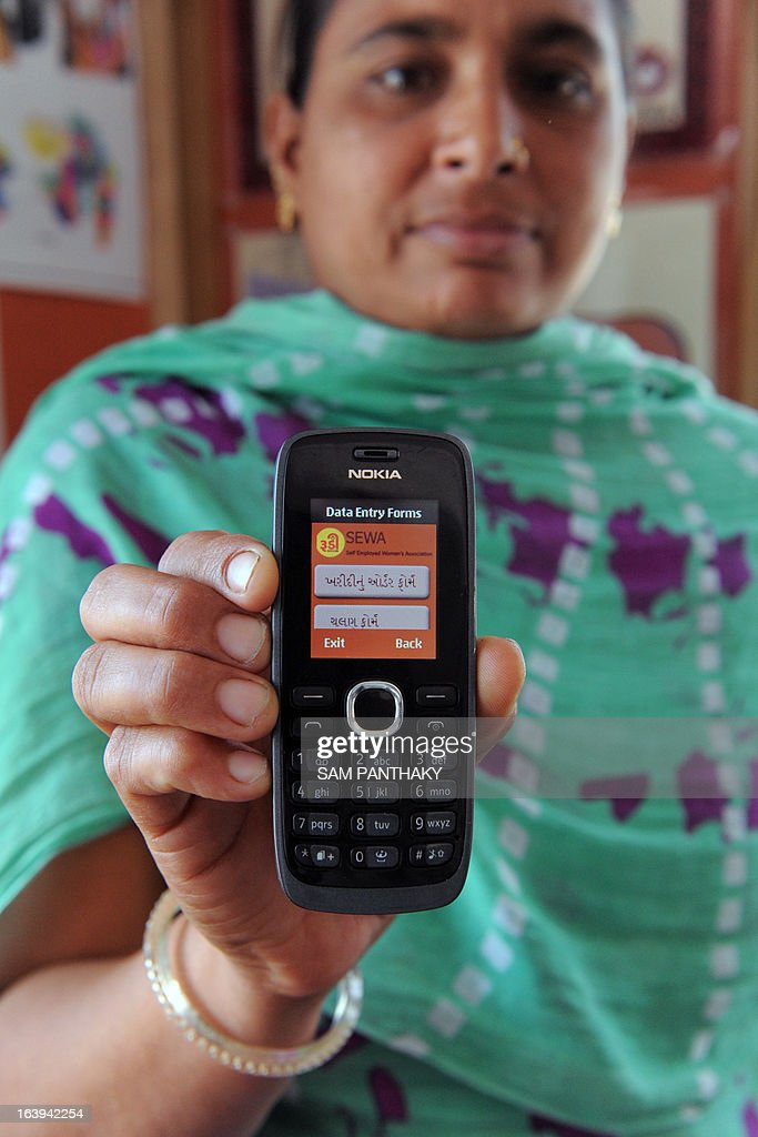 An Indian saleswoman from the Rural Distribution Network India, from the Self Employed Women's Association (SEWA), poses with a mobile phone with an application to place orders via SMS used to maintain agricultural business inventory at Dhragandhra town, some 120 kms from Ahmedabad, on March 18, 2013. Cherie Blair, the wife of former British prime minister Tony Blair, together with Vodafone Foundation director Laura Turkington and SEWA director Reema Nanavaty, are scheduled to visit the RUDI - SEWA centre on March 19. AFP PHOTO / Sam PANTHAKY