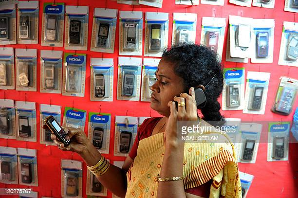 An Indian saleswoman speaks on a cellular telephone as she makes a recharge to a prepaid telephone at a shop in Hyderabad on June 2 2011 With the...