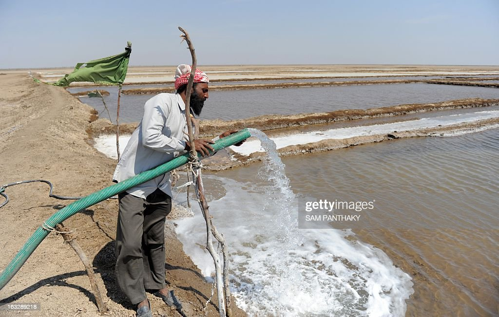 An Indian salt flat worker checks a water pipe in the Santalpur region of Little Rann of Kutch, some 240 kms from Ahmedabad on March 7, 2013. Thousands of salt workers are deprived of basic amenities and the future of their children is uncertain as many schools lack adequate and experienced teaching staff. AFP PHOTO / Sam PANTHAKY