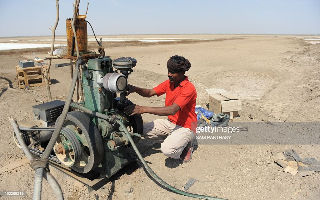 An Indian salt flat worker checks a water pump in the Santalpur region of Little Rann of Kutch, some 240 kms from Ahmedabad on March 7, 2013. Thousands of salt workers are deprived of basic amenities and the future of their children is uncertain as many schools lack adequate and experienced teaching staff. AFP PHOTO / Sam PANTHAKY