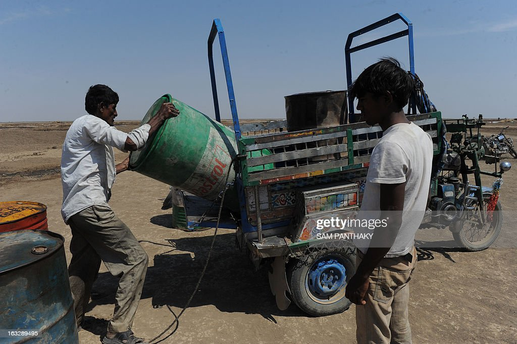An Indian salt flat worker unloads a barrel of diesel to be used to for water pumps in salt flats in the Santalpur region of Little Rann of Kutch, some 240 kms from Ahmedabad on March 7, 2013. Thousands of salt workers are deprived of basic amenities and the future of their children is uncertain as many schools lack adequate and experienced teaching staff. AFP PHOTO / Sam PANTHAKY