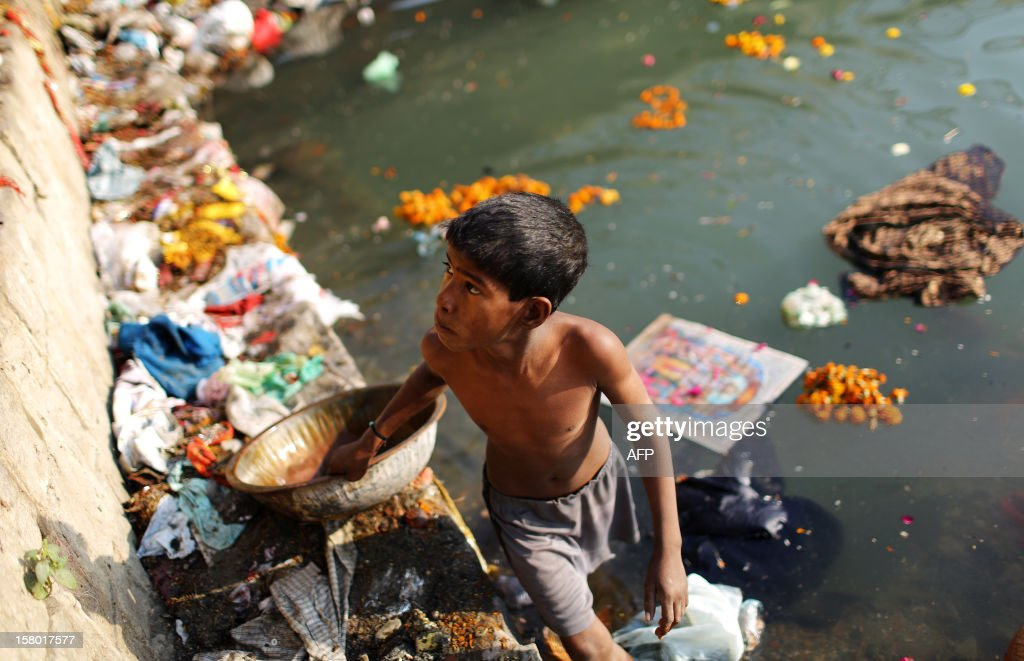 An Indian scavenger looks for recyclable items near a Hindu bathing site in the polluted Yamuna river in New Delhi on December 9, 2012. India's Supreme Court said on December 8, all parameters of water quality of river Yamuna indicate that it resembles a drain and urged authorities to make it pollution-free. Over 2,400 million liters of untreated sewage flows into the Yamuna every day. AFP PHOTO/ Andrew Caballero-Reynolds