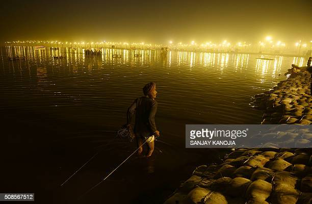 TOPSHOT An Indian scavenger searches for coins offered by Hindu devotees at Sangam during the annual Magh Mela festival in Allahabad on February 5...