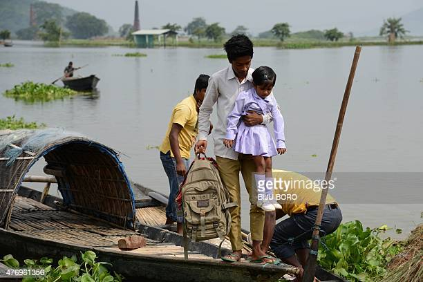 An Indian schoolboy carries his sister from a boat used to navigate floodwater in Rajbari village on the outskirts of Guwahati on June 13 2015...