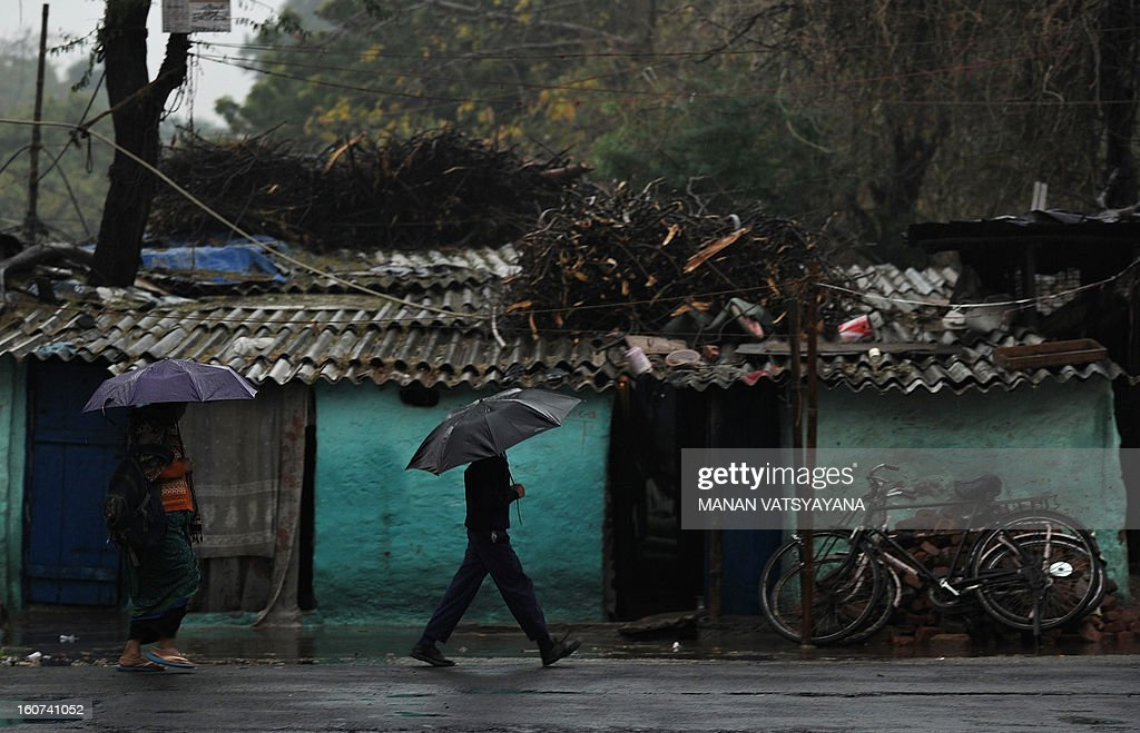 An Indian schoolboy walks with an umbrella during a heavy downpour in New Delhi on February 5, 2013. Heavy rains lashed the Indian capital bringing down the mercury and throwing normal life out of gear. AFP PHOTO/ MANAN VATSYAYANA