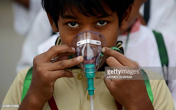 An Indian schoolchild adjusts his facemask before the start of an event to spread awareness of the problem of air pollution in New Delhi on June 4 on...