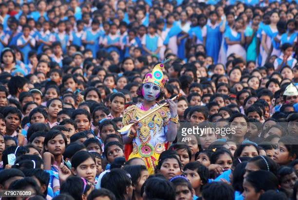 An Indian schoolchild dressed as the Hindu god Krishna and adorned with coloured powder stands among other students during celebrations for the...