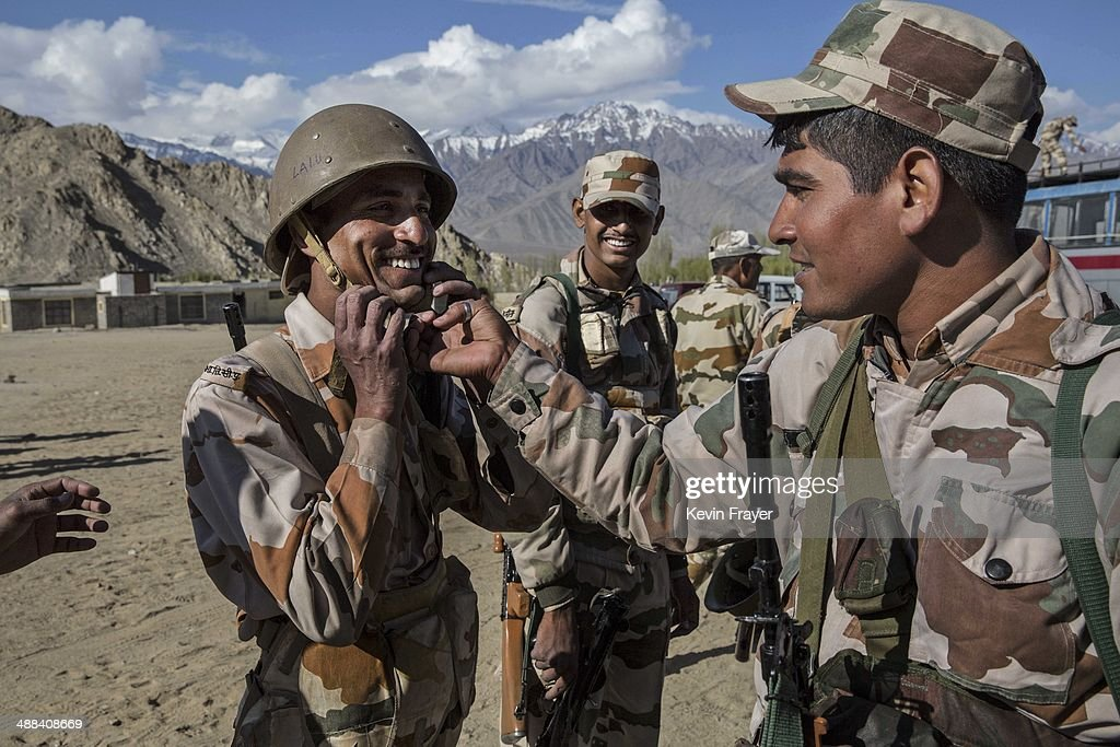 An Indian security force soldier has his helmet adjusted by another as they wait to leave on election duty from a central collection point to head to secure polling stations, on May 6, 2014 in Leh, Ladakh, India. India is in the midst of a nine phase election that began on April 7th and ends on May 12th. Ladakh voters will vote on May 7th.