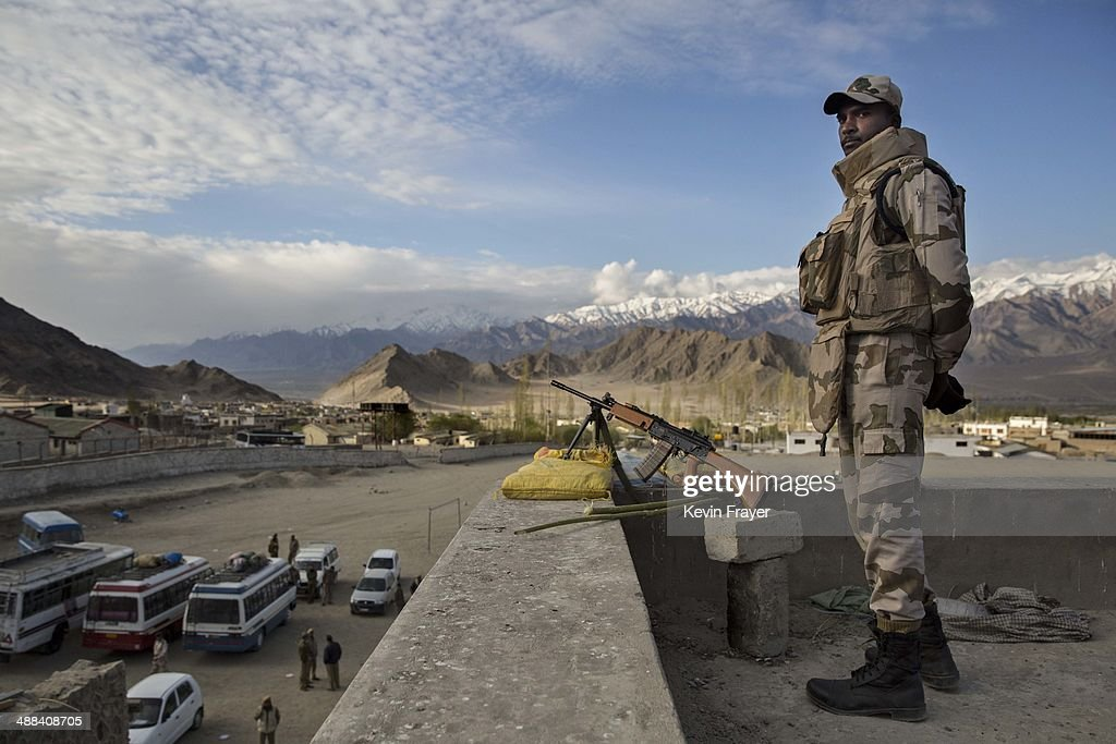 An indian security force soldier stands guard on a rooftop at a central collection point for distribution of voting machines for polling stations on...